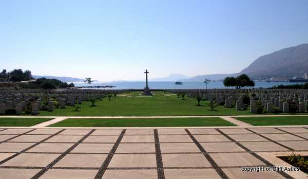 Suda Bay War Cemetery, with tourist boat in foreground.